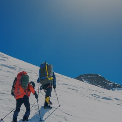 two hikers climbing a snowy mountain