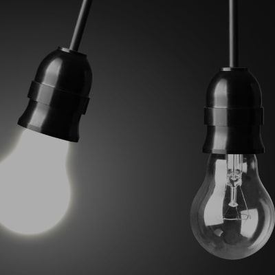two lightbulbs (one lit and one unlit)