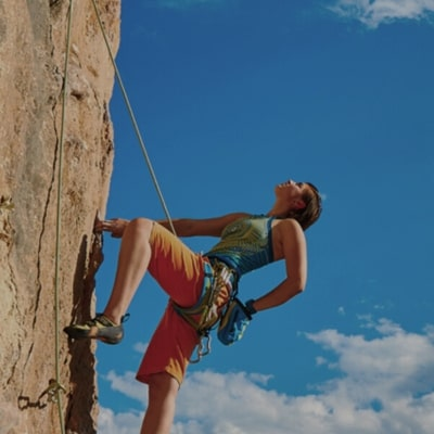 female rock climbing on a sunny day