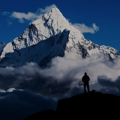 man staring up at a snowy mountain