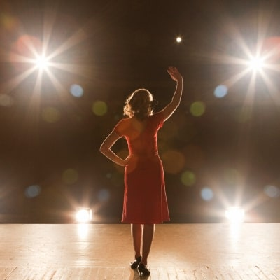 woman standing on stage in front of lights