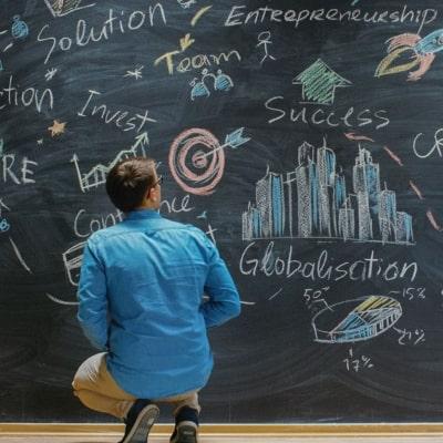 man brainstorming in front of chalkboard