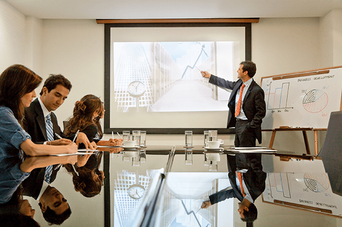 businessman presenting in front of a projector in a boardroom