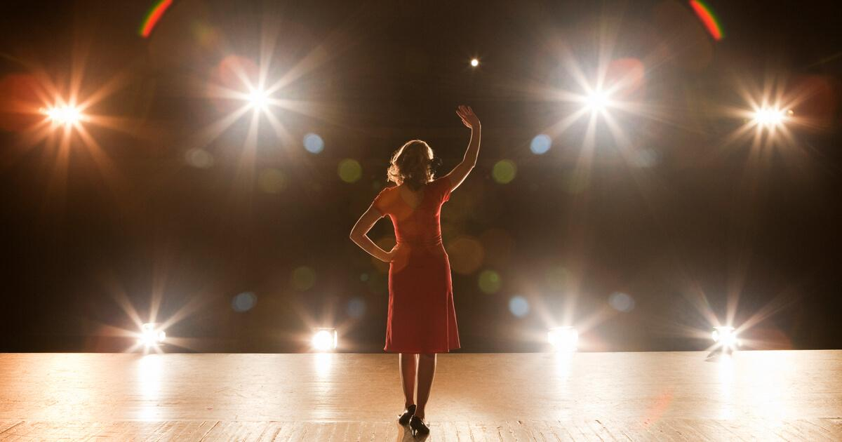 women standing on stage in front of lights