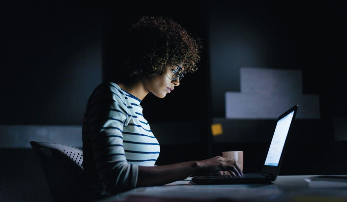 Business woman working on laptop in the dark