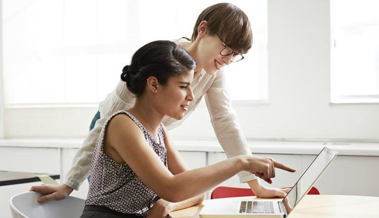 women working on computer with her female colleague standing over her
